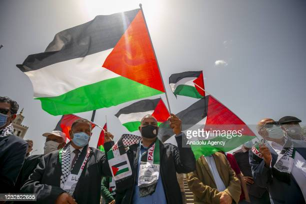 People holding Palestinian and Tunisian flags stage a demonstration to protest attacks by Israeli police with tear gas, rubber bullets and stun...
