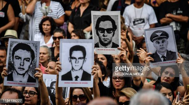 People holding pictures of persons who were killed or went missing during the 19641985 dictatorship demonstrate on the 55th anniversary of the...