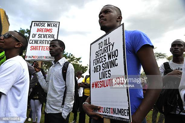People holding placards attend a Musical concert in honour of the victims of the attack on Garissa University College in downtown Nairobi on April 14...