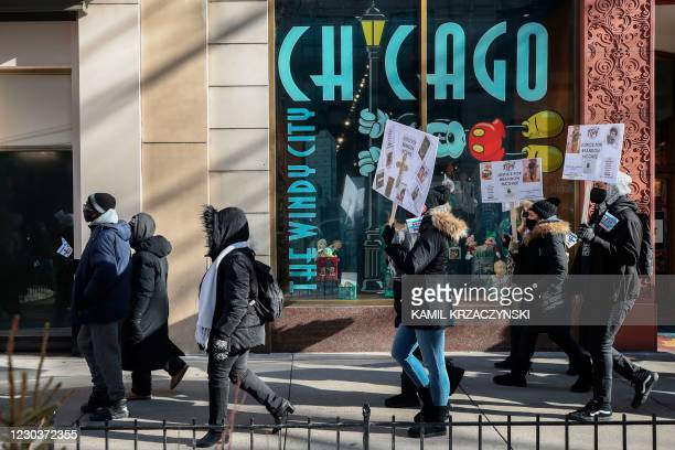 People holding placards, walk during an anti gun violence march on the Magnificent Mile in Chicago, Illinois, on December 31, 2020. - In Chicago,...
