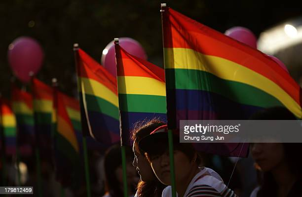People holding rainbow flags attend director Kim Jho KwangSoo and Kim SeungHwan's wedding as the first samesex couple to get married in South Korea...