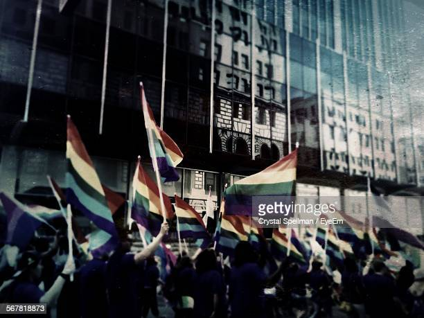People Holding Rainbow Flags During Gay Pride Parade In City At Night