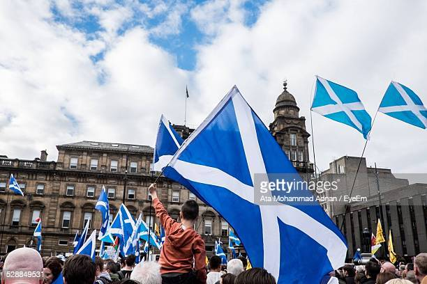 people holding scottish flags - scotland flag stock photos and pictures