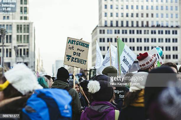people holding sign board with text in city - march stock-fotos und bilder