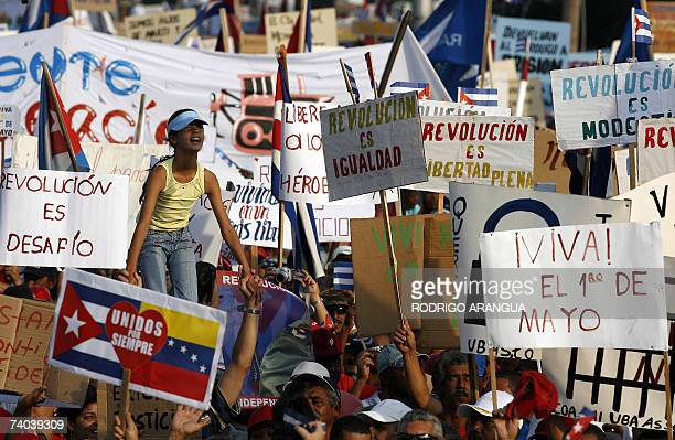 People holding signs march at the Revolution Square in Havana during the May Day parade 01 May 2007 Cuban President Fidel Castro was a noshow Tuesday...