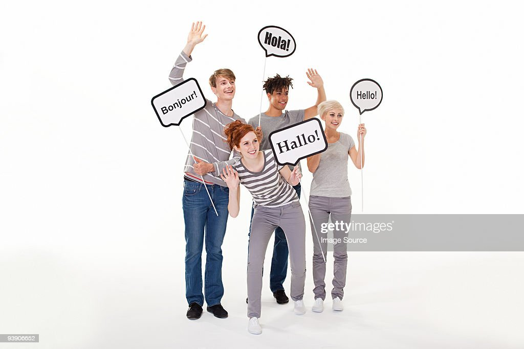 People holding signs that say hello in different languages : Stock Photo