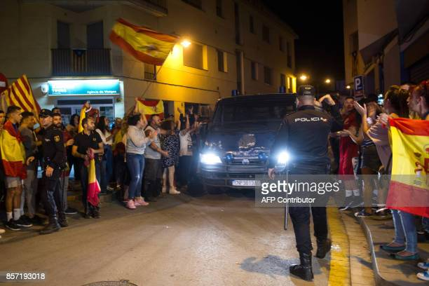 People holding Spanish and Catalan flags applaud as a Spanish National police van leaves the Hotel MontPalau in Pineda de Mar on October 3 where...