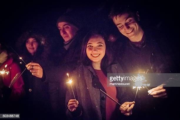 people holding sparkling bengal fire outdoors at night in winter. - bengal new year stock photos and pictures