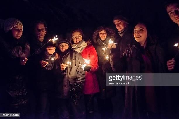 Persone con scintillanti Bengala Fuoco all'aperto di notte in inverno.