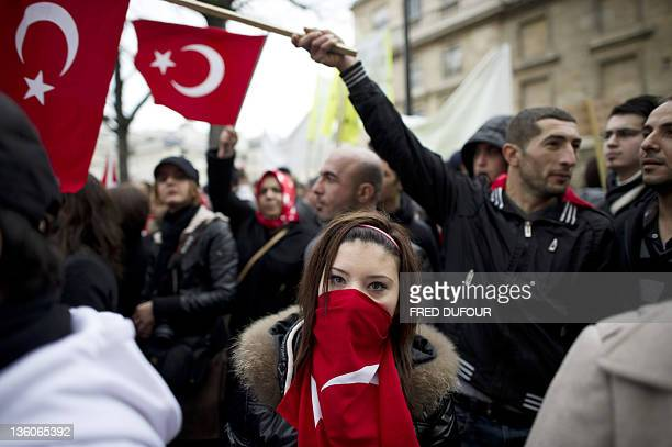 People holding the Turkish flag take part in a rally next to the French National Assembly on December 22 2011 in Paris as the French parliament is...