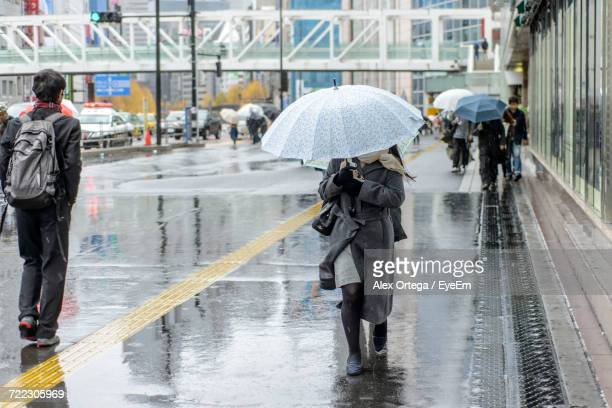 People Holding Umbrella Walking On Footpath In City