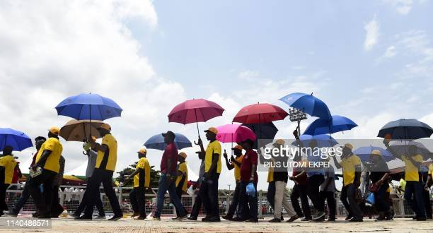 People holding umbrellas march and gesture during the International Workers' Day, also known as Mayday at the Agege Stadium in Lagos, on May 1, 2019....