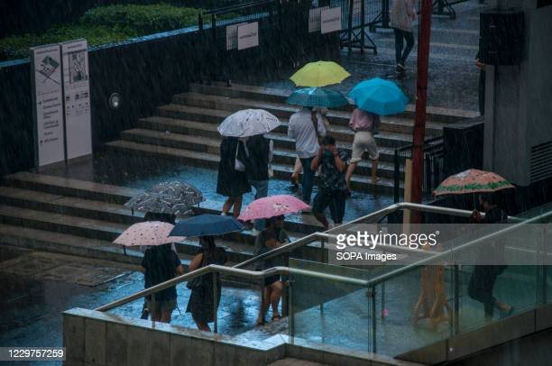 People holding umbrellas move up the stairs near Ratchadamri Road on a Rainy Day.