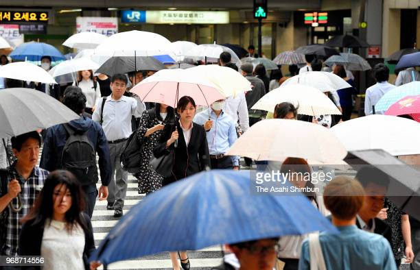 People holding umbrellas walk in front of Osaka Station on June 6 2018 in Osaka Japan Japan Meteorological Agency said that compared with last year...