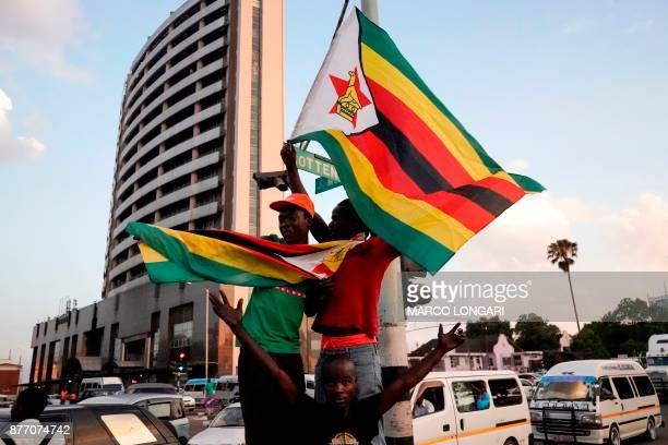 People holding Zimbabwean flags celebrate in the street after the resignation of Zimbabwe's president Robert Mugabe on November 21 2017 in Harare Car...