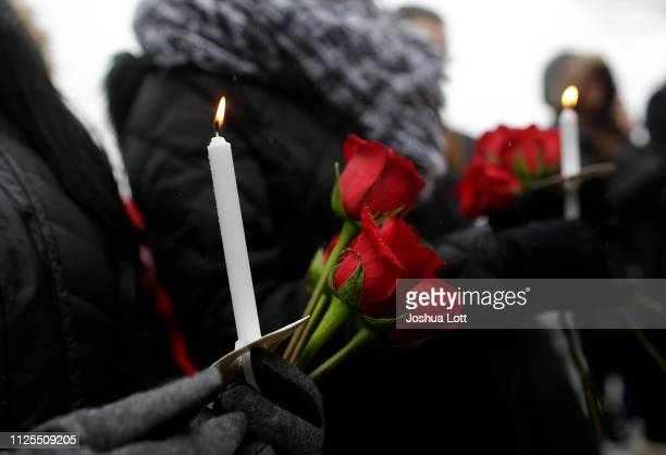 People holds candles as they attend a prayer vigil outside Henry Pratt Company on February 17 2019 in Aurora Illinois Six people including a gunman...