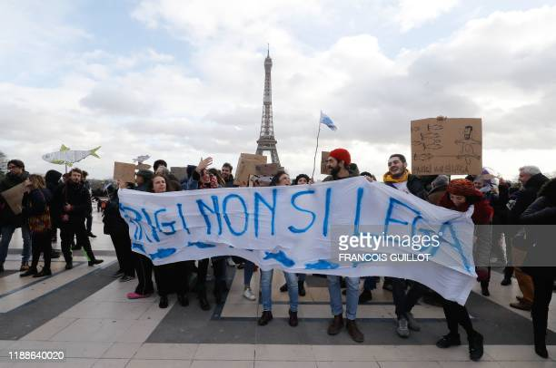 People holds cardboards depicting fishes and a banner reading Can't tie Paris during a demonstration of the Sardine Movement formed to oppose the...