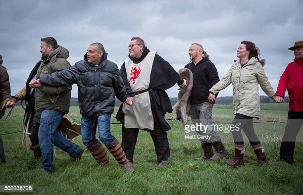 People holds hands in a ceremony being held outside the stones as druids pagans and revellers gather at Stonehenge hoping to see the sun rise as they...