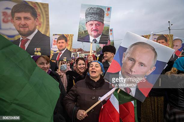People holds pictures of Russian President Vladimir Putin first Chechen President Akhmad Kadyrov and Head of Chechen republic Ramzan Kadyrov during a...
