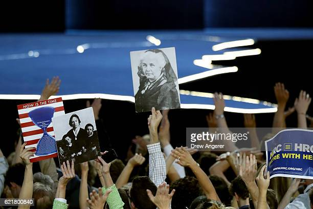 People holds posters of women's rights activist Elizabeth Cady Stanton as they watch voting results at Democratic presidential nominee former...