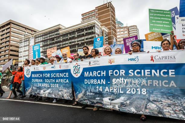 People holds up a banner during the 'March for Science' in Durban on April 14 organised by the University of KwaZuluNatal the South African Medical...