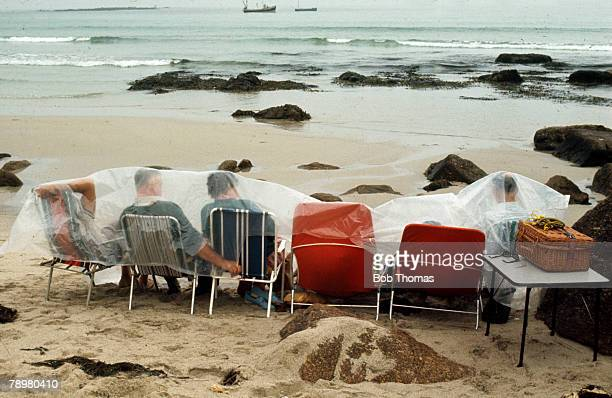 1970 Hardy holidaymakers hoping for a picnic have to endure the British climate as they take shelter on the beach by covering themselves in a plastic...