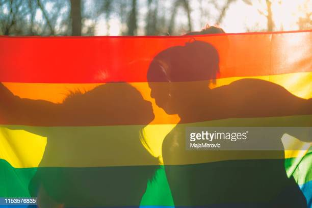 people, homosexuality, same-sex marriage, gay and love concept - close up of happy lesbian couple holding hands over rainbow flag - lesbica imagens e fotografias de stock
