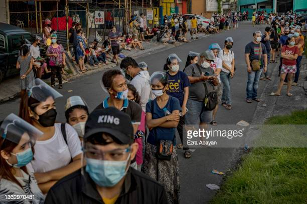 People hoping to get vaccinated against COVID-19 queue outside a vaccination site on August 08, 2021 in Las Pinas, Metro Manila, Philippines. As a...