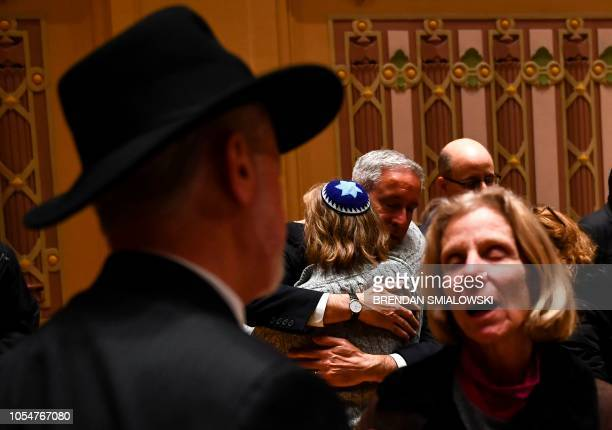 People hug after a vigil to remember the victims of the shooting at the Tree of Life synagogue the day before at the Allegheny County Soldiers...