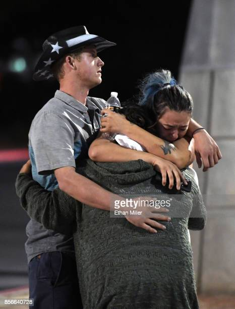 People hug and cry outside the Thomas Mack Center after a mass shooting at the Route 91 Harvest country music festival on October 2 2017 in Las Vegas...