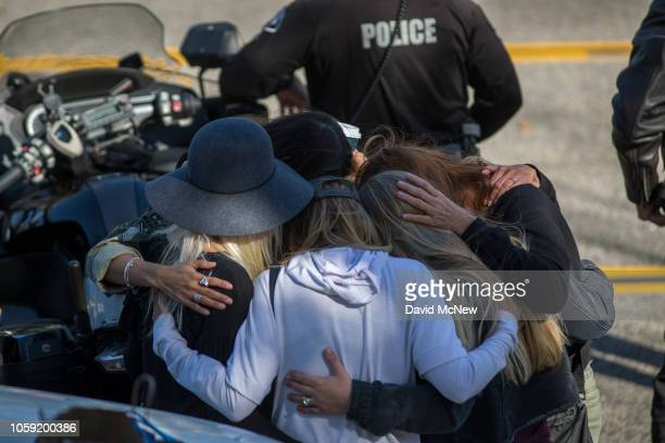 People hug and pray before the procession carrying the body of Ventura County Sheriff Sgt. Ron Helus, who was killed in a mass shooting at the...