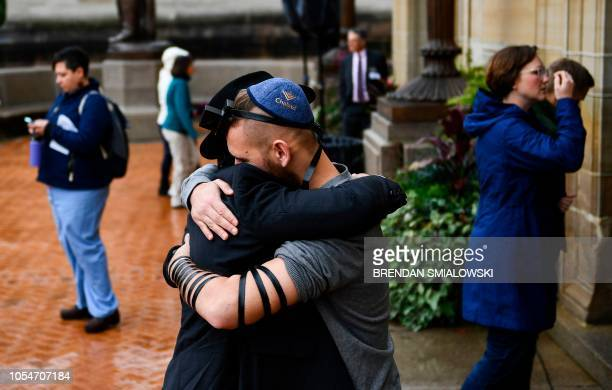 People hug as they arrive for a vigil for the shoting at the Tree of Life synagogue the day before at the Allegheny County Soldiers Memorial on...