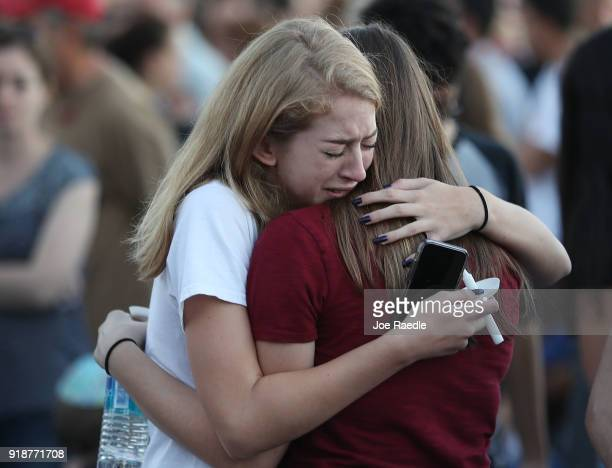 People hug as they attend a candlelight memorial service for the victims of the shooting at Marjory Stoneman Douglas High School that killed 17...