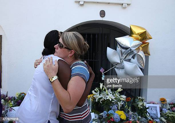 People hug as they pay their respects in front of Emanuel African Methodist Episcopal Church after a mass shooting at the church that killed nine...