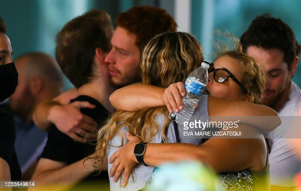 People hug as they wait for news about relatives at the Community Center in Surfside north of Miami Beach, Florida on June 25, 2021. - Four people...