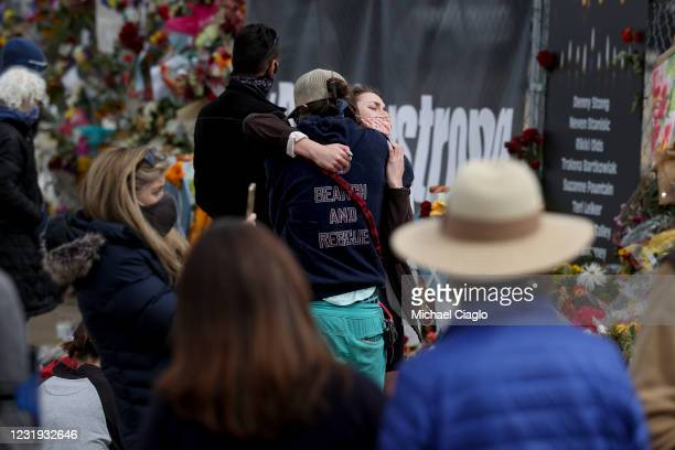 People hug at a makeshift memorial outside a King Soopers grocery store on March 25, 2021 in Boulder, Colorado. Ten people, including a police...