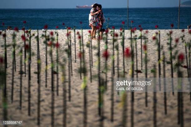 People hug behind roses placed by the NGO Rio de Paz on Copacabana beach, Rio de Janeiro, in memory of Brazil's half a million COVID-19 victims, on...