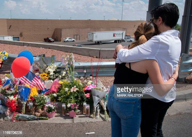 People hug beside a makeshift memorial outside the Cielo Vista Mall WalMart where a shooting left 20 people dead in El Paso Texas on August 4 2019...