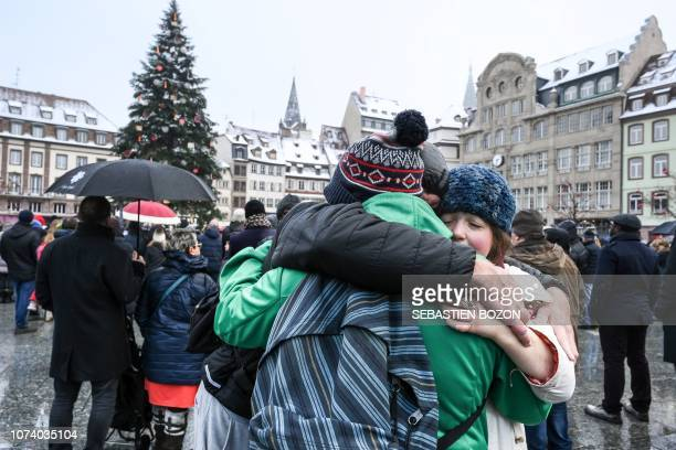 People hugh each others as they attend a gathering around a makeshift memorial at Place Kleber in Strasbourg on December 16 2018 to pay a tribute to...