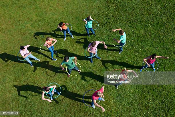 People hula hooping on grass
