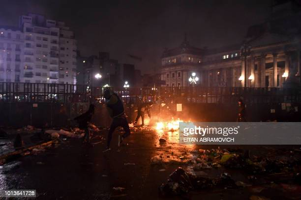 People hurl stones and bottles to riot police agents outside the National Congress in Buenos Aires on August 9 after senators rejected the bill to...