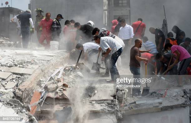 TOPSHOT People hurry to free possible victims out of the rubble of a collapsed building after a quake rattled Mexico City on September 19 2017 A...