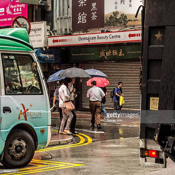 CONTENT] People hurrying across the street during a sudden rainfall in Wan Chai Hong Kong