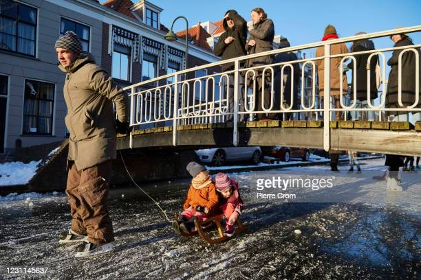 People ice skate and sled on the frozen canals on February 13, 2021 in Delft, Netherlands. Parts of central and northern Europe and Britain have...