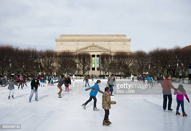 People ice skate at the National Gallery of Art's Sculpture Garden ice rink adjacent to the National Archives in Washington DC December 21 2016 / AFP...