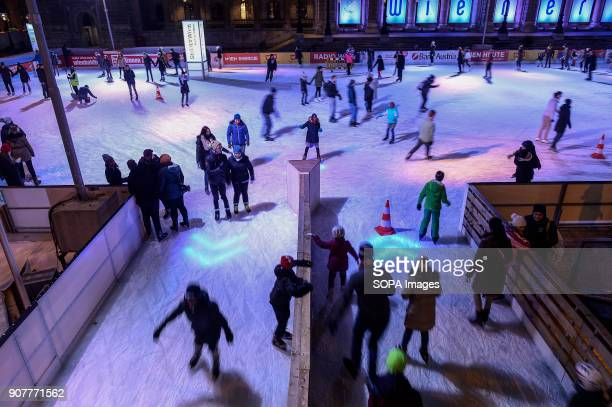 People ice skate in front of Vienna city hall