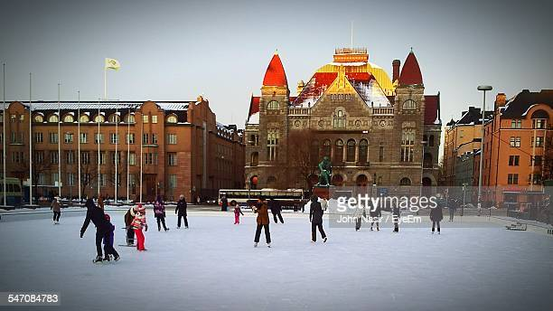 People Ice Skating Against Historic Buildings In City