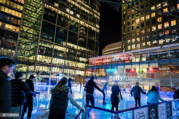 People ice skating at Canary Wharf ice rink, London, UK