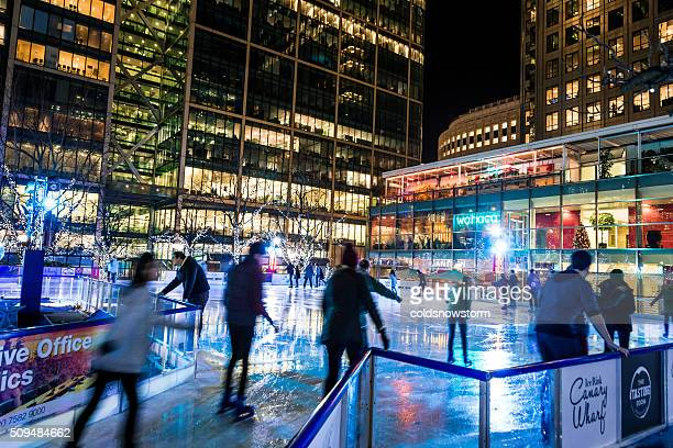 people ice skating at canary wharf ice rink, london, uk - canary wharf stock photos and pictures