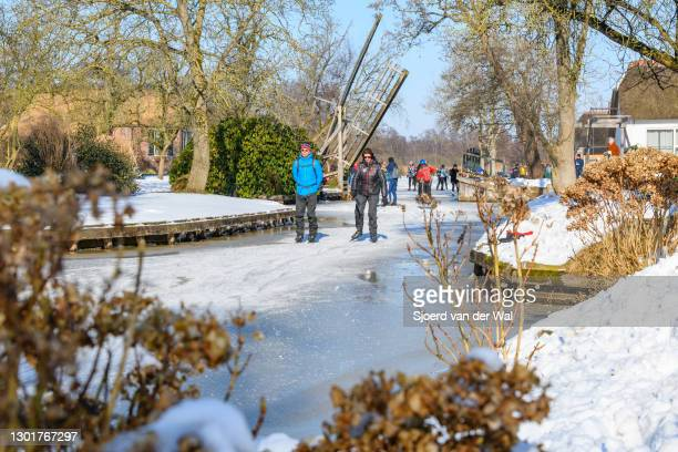 People ice skating on a frozen canal in the Dwarsgracht near Giethoorn in the Weerribben-Wieden nature reserve in Overijssel during a cold winter day...